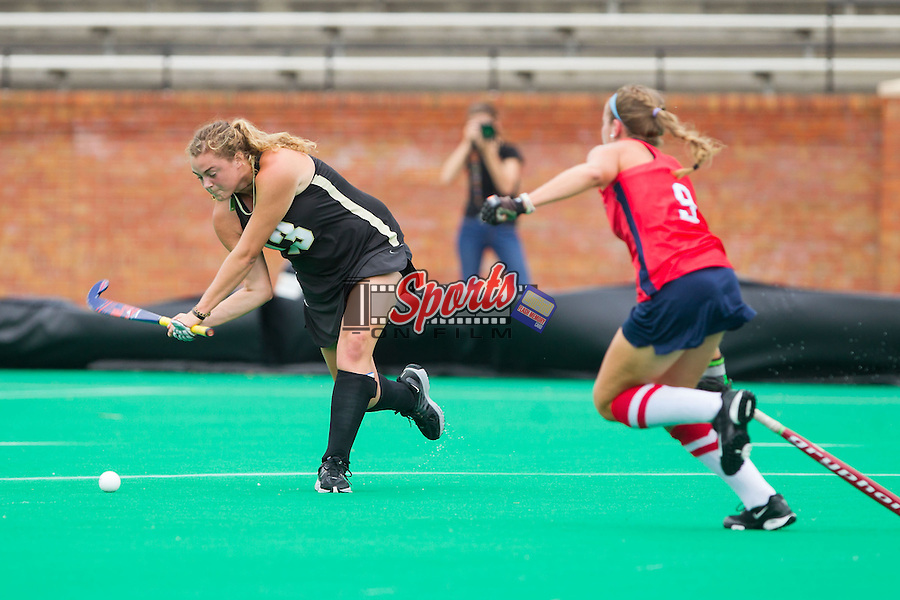 Jess McFadyen (13) of the Wake Forest Demon Deacons winds up to take a shot on goal as Jessica Hollis (9) of the Richmond Spiders rushes towards her at Kentner Stadium on September 29, 2013 in Winston-Salem, North Carolina.  The Demon Deacons defeated the Spiders 1-0 in overtime.  (Brian Westerholt/Sports On Film)
