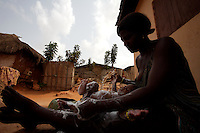 """a child, is being washed by his mother a  former """"trokosi"""" religious slaves,  and still connected to the shrine just outside the shrine  in Kilkor, in the Volta region, Ghana on Friday March 09 2007.."""