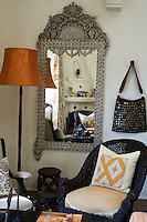 A studded leather bag hangs on the living room wall next to an ornate inlaid mother of pearl mirror