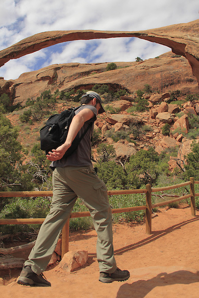 Man hiking under Landscape Arch in Arches National Park, Utah, USA .  John offers private photo tours in Arches National Park and throughout Utah and Colorado. Year-round.