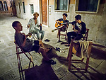 Young adults relax for midnight music and home-made wine, Venice, Italy