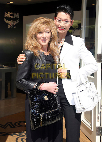KELLY HOPPEN & SUNGJOO KIM.Renowned interior designer Kelly Hoppen has joined forces with luxury brand MCM to create an elegant boudoir in their new London showroom in Sloane Stret, Knightsbridge, London, England, UK, 22nd May 2008..half length black leather jacket bag white bags .CAP/DS.©Dudley Smith/Capital Pictures