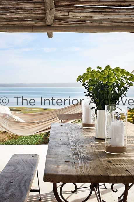 A hammock is suspended on a covered terrace affording a view to the beach. A wooden table and chairs provide an outdoor dining area.