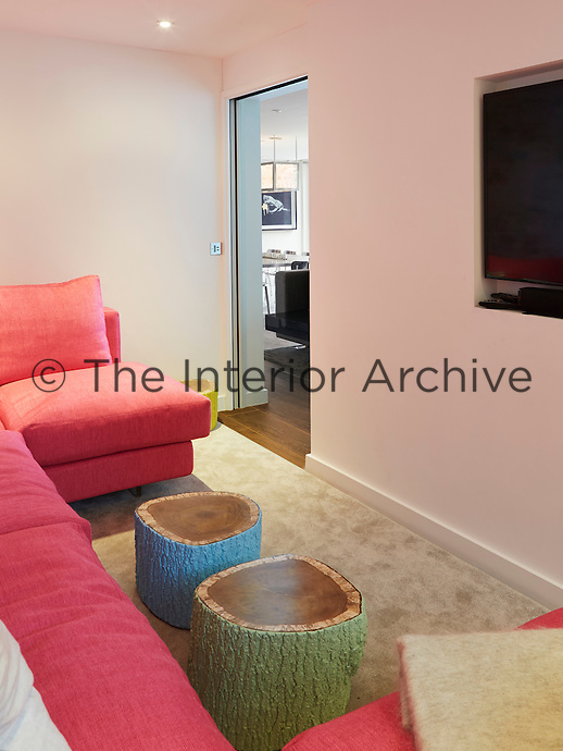 A cosy, children's television room in pink tones is situated off the main sitting area and is furnished with painted tree trunk coffee tables and a comfortable sofa.
