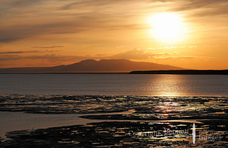 The sun sets over Mt. Susitna, also known as Sleeping Lady, as seen from the Alaska Railroad as it approaches Anchorage.