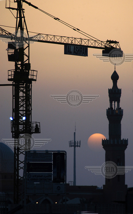 The sun sets behind a mosque's minaret and a construction crane on Sheikh Zayd Road. About 30,000, or 24 per cent of the world's 125,000 construction cranes are currently operating in Dubai