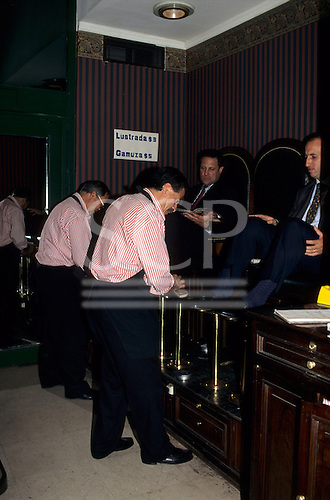 Buenos Aires, Argentina. Businessmen having their shoes shined by men in uniform in plush surroundings.