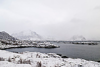 Snow covered skerries and  distant mountains rise from Vestfjorden near Stamsund, Lofoten Islands, Norway