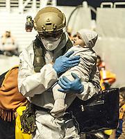 Un fuciliere di Marina porta in salvo un neonato durante un soccorso nel Canale di Sicilia.