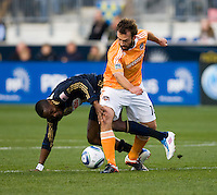 Danny Mwanga (10) of the Philadelphia Union fights for the ball with Adam Moffat (16) of the Houston Dynamo during the game at PPL Park in Chester, PA.  Houston defeated Philadelphia, 2-1, to take home the one goal advantage in the home and home series..