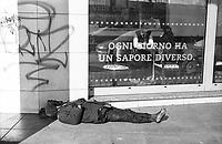 """Milano, periferia nord. Un senzatetto, scalzo, dorme davanti alla vetrina di un ristorante con la scritta """"ogni giorno ha un sapore diverso"""" --- Milan, north periphery. A homeless, barefoot, sleeping on the ground in front of the window of a restaurant with the writing """"every day has a different taste"""""""
