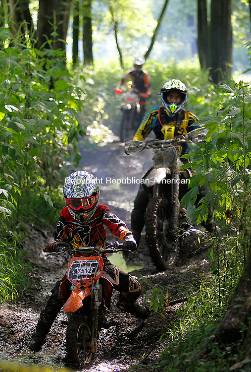 THOMASTON, CT - 19 AUGUST 2017 - 081917JW04.jpg -- Amber Grenewicz makes her way through the muddy trails watched by Pathfinders MC course chasers during the Pathfinders Motorcycle Club of Connecticuts Dam Good National Hare Scramble Saturday morning at Thomaston Dam. Riding continues Sunday with the PRO/AM series. Jonathan Wilcox Republican-American