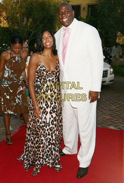 "COOKIE JOHNSON & EARVIN ""MAGIC"" JOHNSON .11th Annual DesignCare event benefiting the HollyRod Foundation held at a Private Residence, Beverly Hills, CA, USA..July 25th, 2009.full length white suit pink tall short leopard print dress tie long maxi married husband wife.CAP/ADM/TL.©Tony Lowe/AdMedia/Capital Pictures."