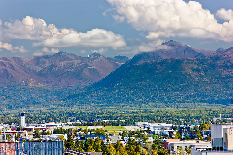 Small plane taking off from Merril Field flying in front of the Chugach Mountains, Fall, Anchorage, Southcentral Alaska, USA.