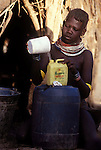 A Turkana woman pours water into  a manageable container.  She has collected  the water from a nearby  water source...Northern Kenya.....