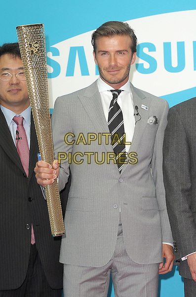 David Beckham.Samsung kicks-off its London 2012 campaign 'Everyone's Olympic Games', Canary Wharf, London, England..13th June 2011.half length grey gray suit jacket stubble beard facial hair torch gold.CAP/BEL.©Tom Belcher/Capital Pictures.