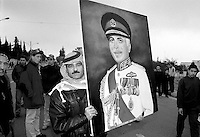 Amman, Jordan a man carrying a portrait of  King Hussein makes his way to the funeral of the king in the streets of Amman, February 8,1999. Photo by Quique Kierszenbaum