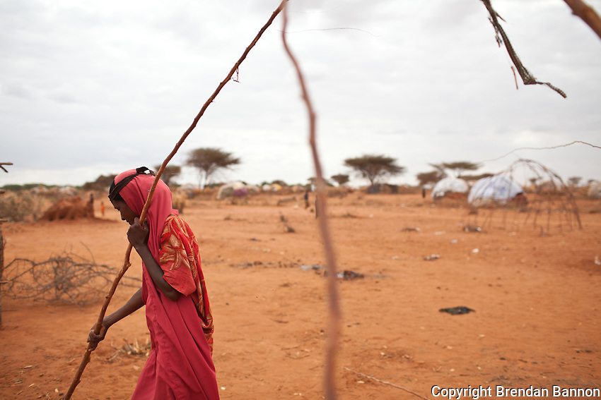 """Haretha Abdi, a Somali nomad arrived in Kenya s a refugee with her husband and five Children in Ifo extention on July 6, 2011.  The made a choice, """"due to hunger, draught and war we chose to pack for Kenya. Along the way we would either meet people  who helped us or sleep hungry."""" she said. She is building a traditional tukol for her family in the self settled area atthe outskirts of Ifo camp in Kenya."""