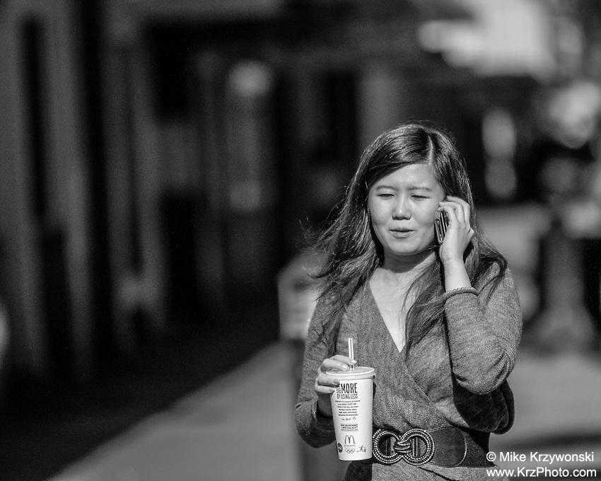 Asian business woman on cell phone holding a drink while walking in downtown Honolulu, Oahu, Hawaii