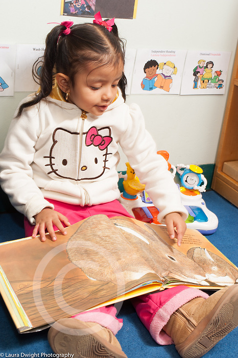 """Education preschool 3 year olds girl sitting and """"reading"""" picture book, talking and pointing at illustration, holding book upside down"""
