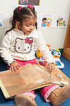 "Education preschool 3 year olds girl sitting and ""reading"" picture book, talking and pointing at illustration, holding book upside down"