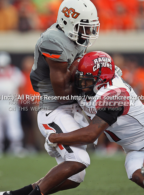 Oklahoma State Cowboys running back Joseph Randle (1) and Louisiana-Lafayette Ragin Cajuns linebacker Devon Lewis-Buchanan (11) in action during the game between the Louisiana-Lafayette Ragin Cajuns and the Oklahoma State Cowboys at the Boone Pickens Stadium in Stillwater, OK. Oklahoma State defeats Louisiana-Lafayette 61 to 34.