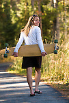 A young woman walks with her skateboard in Jackson Hole, Wyoming.