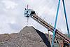 Industrial conveyor belt transporting and piling up scrap metal at Liverpool Docks England,