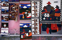 Woven rugs in a variety of traditional bold designs exhibited for sale against a wall in the market at Saquisili, which is in Ecuador's Avenue of the Volcanoes.