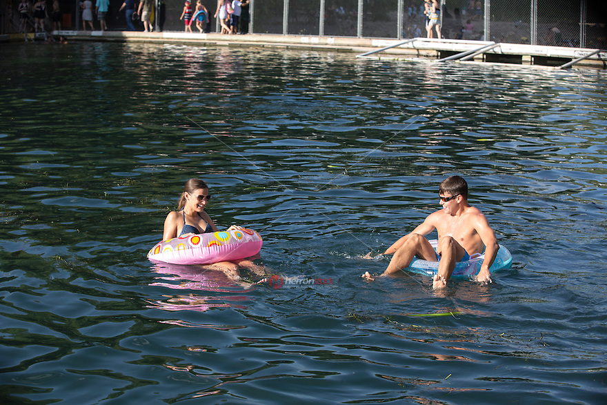 Austin couple swims at Barton Springs Pool. Within Zilker Park's 358 acres lies one of the crown jewels of Austin - Barton Springs Pool. The pool itself measures three acres in size, and is fed from underground springs with an average temperature of 68-70 degrees, ideal for year-round swimming.