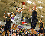 SIOUX FALLS, SD - JANUARY 2:  Tom Aase #14 from the University of Sioux Falls takes the ball to the basket between Casey Schilling #32 and Daniel Jansen #34 from Augustana in the first half of their game Friday night at the Stewart Center. (Photo by Dave Eggen/Inertia)
