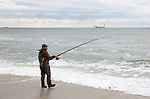 Tim Firrman of Brick, NJ fishes for Striped Bass on the beach in Mantoloking, New Jersey.  In the background is the barge being used by the Army Corp of Engineers as they work on dune construction on the beach in Mantoloking, New Jersey. (Bill Denver For New York Daily News)