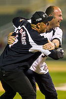 Slugger Labbe (35) of Team NASCAR (right) grabs Bob Vandergriff (10) of Team NHRA as he tries to score a run in the NASCAR vs NHRA Charity Softball Challenge at CMC-Northeast Stadium on April 17, 2013 in Kannapolis, North Carolina.  Team NHRA defeated Team NASCAR 19-5.  (Brian Westerholt/Four Seam Images)