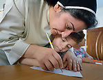 Sister Ferdos Zora helps a student draw in a preschool for displaced children run by the Dominican Sisters of St. Catherine of Siena in Ankawa, near Erbil, Iraq.<br /> <br /> The children, and the nuns themselves, were displaced by ISIS from Mosul and Qaraqosh in 2014. The sisters have established a variety of schools and other ministries among the displaced.