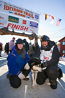 Tom Lesatz and his girl friend and kennel partner Jessica Hendricks pose with their leader at the finish chute on Front street