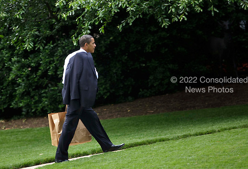 "Washington, DC - May 29, 2009 -- United States President Barack Obama holding his take-away lunch bags from a ""Five Guys"" burgers and fries restaurant returns to the White House, Friday, May 29, 2009 in Washington, DC.  President Obama traveled with his motorcade to the burger restaurant in Southeast Washington. .Credit: Brendan Smialowski - Pool via CNP"
