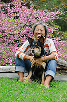 An older local Asian woman and her dog in front of a cherry blossom tree, Pa'auilo Mauka, Big Island.