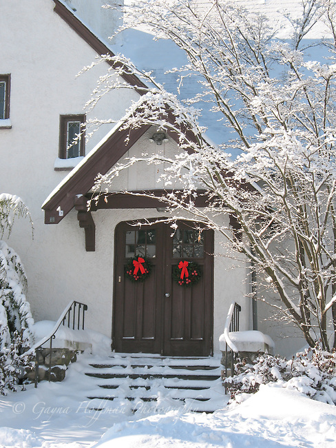 Church doors with wreaths and red bows. Winter, snow.