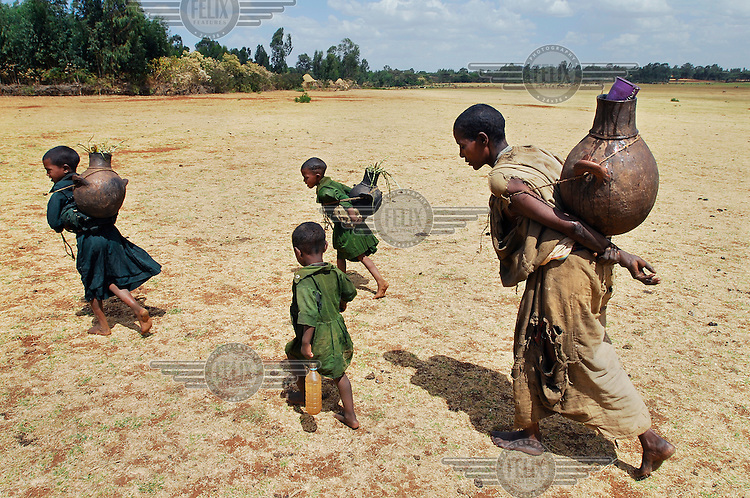 A woman and her children carry water home from a creek.  Over 70 percent of the Ethiopian population has no access to a safe water supply and adequate sanitation.  A severe drought has extended across East Africa after the rainy season expected in October 2005 failed to arrive. Most rural dwellers in the southernmost area of the country rely on two rainy seasons and two dry seasons per year..