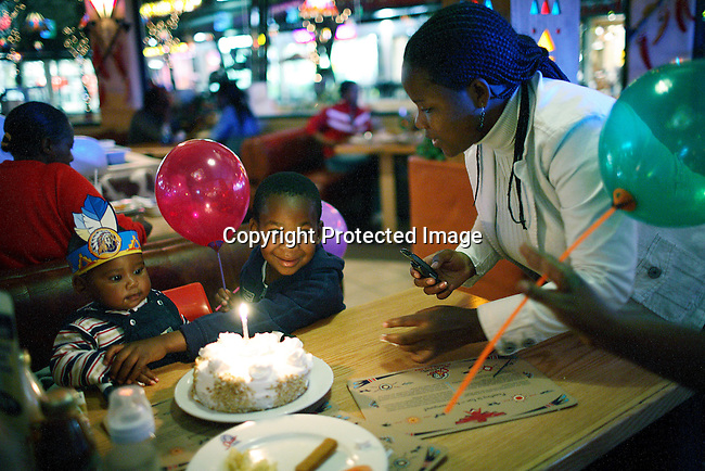 A boy celebrates his 1 year birthday with a cake and a light in a family restautant, with his brother and mother.