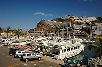 Hotels overlooking harbour and boats at Puerto Mogan, Gran Canaria, Canary Islands, Spain.