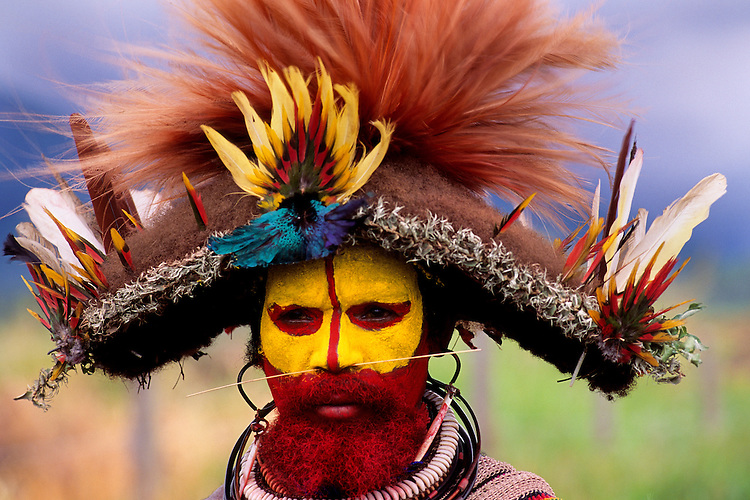 A Huli man wears face paint and a headdress made from the feathers of different birds-of-paradise near the village of Tari in the Southern Highlands Province of Papua New Guinea during sing-sing. Mt Hugan,  Papua New
