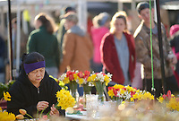 NWA Democrat-Gazette/ANDY SHUPE<br /> Mai Moua of Summers Fresh farm in Summers arranges a bouquet of flowers Saturday, March 31, 2018, while setting up for the Fayetteville Farmers' Market on the Fayetteville square. The market has returned to the square for the season and is open 7 a.m. to 1 p.m. Tuesdays and Thursdays and 7 a.m. to 2 p.m. on Saturdays.