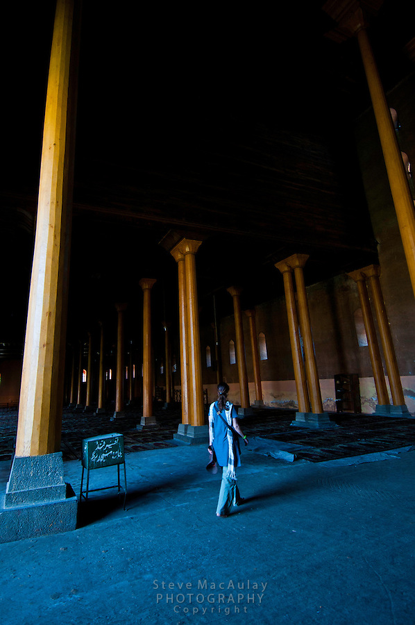 Female western tourist walking among the towering columns hewn from a single deodar tree that support the roof of the massive Jama Masjid Mosque, Srinagar, Kashmir, India.