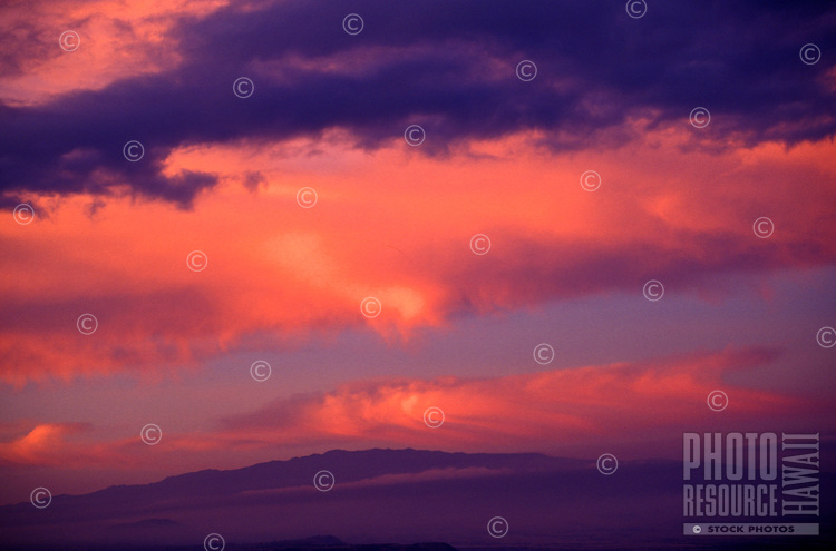 Huge bands of pink and purple clouds hover over Hualalai mountain on the Big Island of Hawaii.