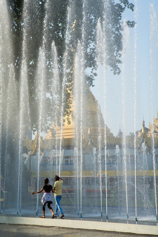 young couple walking in front of fountain near the Sule pagoda, Yangon, Myanmar