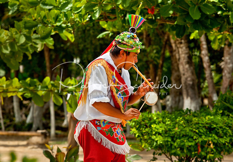 Mexican aerial dancers dressed in colorful traditional clothing entertain travelers to Tulum, the site of archaeological ruins of Tulum (Ruines de Tulum) and the villages popular Mexican markets. Tulum is one of several Mexican tourist districts found in the Mexican state of Quintana Roo. The dance, called the Flying Men Dance or Danza del Volador, is performed for donations or tips. Wearing traditional attire, the dancers climb to the top of a pole (approximately 100 feet tall), fasten ropes to their bodies then spin, rotating around until they reach the ground.