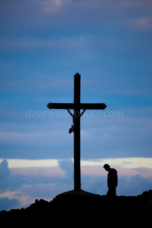 Man praying at a crucifix beside the  Mediterranean in Collioure, Pyrénées-Orientales, in the Roussillon province in the South of France.