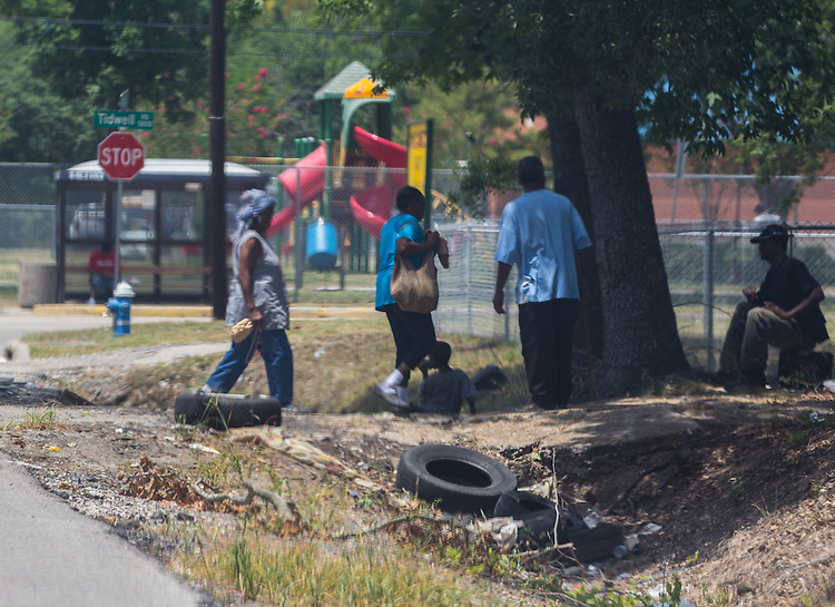 People are loitering under a tree on Grady, directly across from Shadydale Elementary. They appear to be drinking in front of a child. Trash, including old tires, is also littering the area.