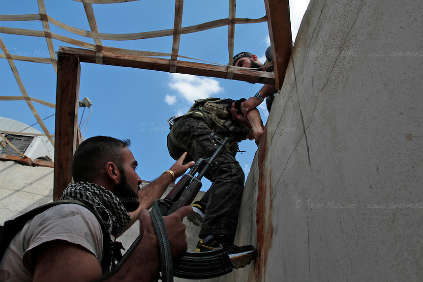 Free Syria Army soldiers move into position to attack a building housing several Assad forces during urban fighting in the al-Amaria district of Aleppo...© Javier Manzano.